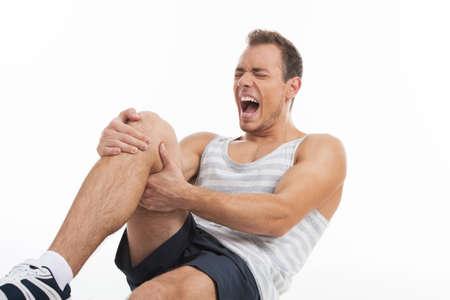 dolor de rodilla: Hombre que grita de un dolor en la rodilla. Aunque aislados en blanco Foto de archivo