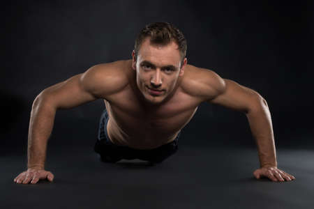 Handsome Young sport man. Fitness muscle model guy making push ups exercise over black  photo