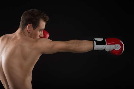thai arts: One Caucasian man exercising boxing. Isolated on black background Stock Photo