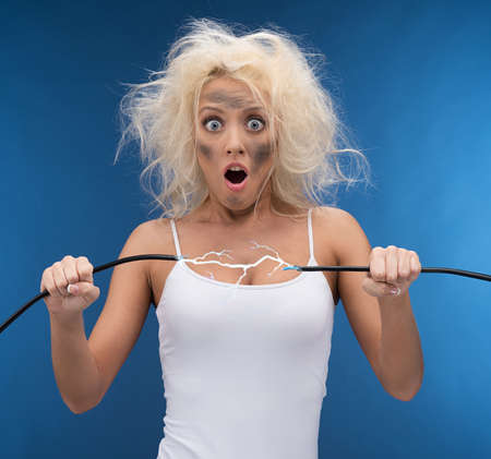 electrical cable: Funny girl having problem with electricity. Electrical shock