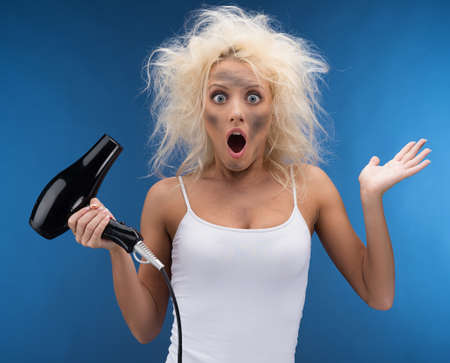 Funny blond girl having problem with hairdryer. Isolated on blue