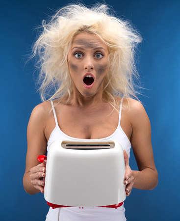 Grappig blond meisje problemen met broodrooster. Geà ¯ soleerd op blauw Stockfoto