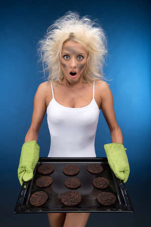 Burnt cookies. Funny blond girl have trouble with cooking photo
