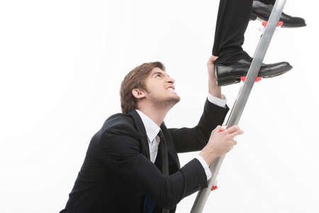 Business competition  Angry young businessman grabbing another men� leg rising up by stairs photo