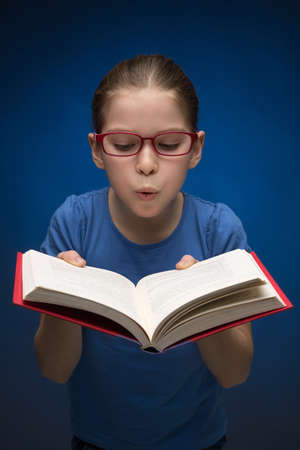 preadolescence: Pretty schoolgirl with book. Pretty little girl in glasses holding an open book and blowing on it a while standing isolated on blue  Stock Photo