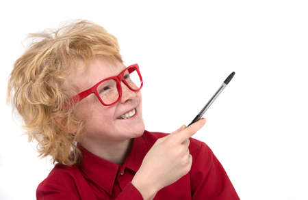 preadolescence: Boy in red glasses. Cheerful red hair boy in glasses pointing away with a pen and smiling while isolated on white