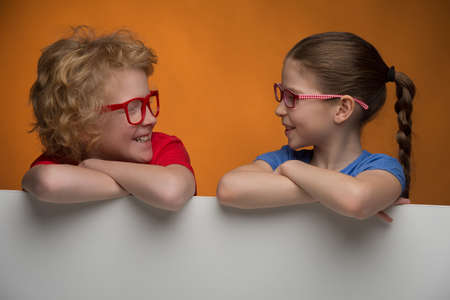 preadolescence: Happy children. Cheerful children in glasses looking at each other and smiling while standing isolated on coloured