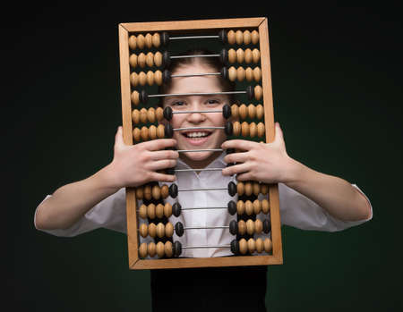 78: Girl with abacus. Happy little girl looking through abacus and smiling while standing isolated on black