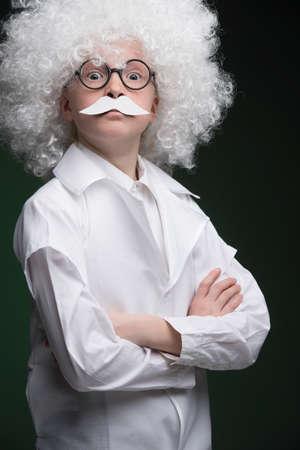Little Einstein. Confident little boy looking like Einstein and standing isolated on black photo