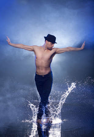 Wet dancer. Young male dancer in black fedora dancing on the wet floor photo