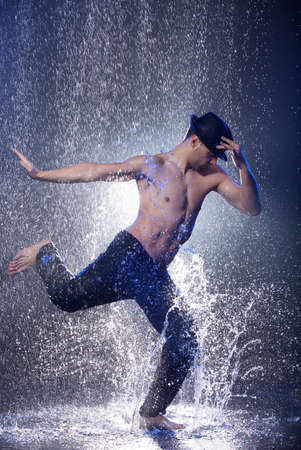 Dancing in the rain. Young male dancer in black fedora dancing in the rain Stock Photo
