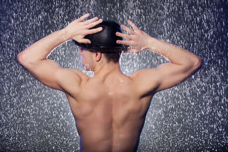 Perfect body. Rear view of young men in black fedora standing under the rain photo