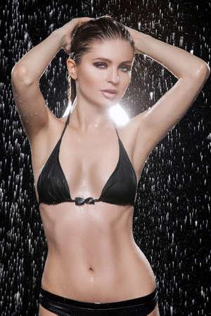 Schöne nasse Frauen Schöne nasse Frauen in schwarzen Bikini posiert unter der regen Standard-Bild - 23307093