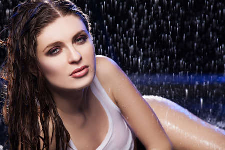 Wet beauty  Beautiful young women looking at camera while lying on the floor under the rain photo