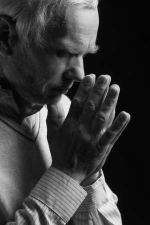 Senior man praying. Black And White image of senior men praying and holding his hands clasped while isolated on black