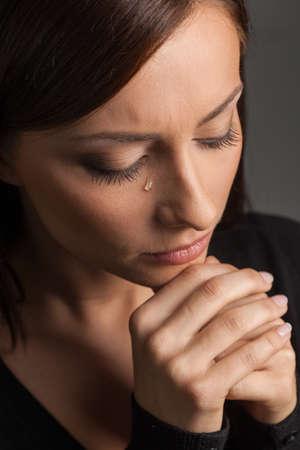 mujer llorando: Las mujeres lloran. Vista superior de la mujer joven llorando mientras aislados en gris Foto de archivo