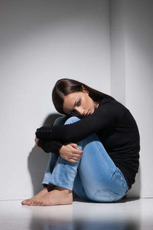 long depression: Depressed women. Young depressed women sitting on the floor and holding her head on knees Stock Photo