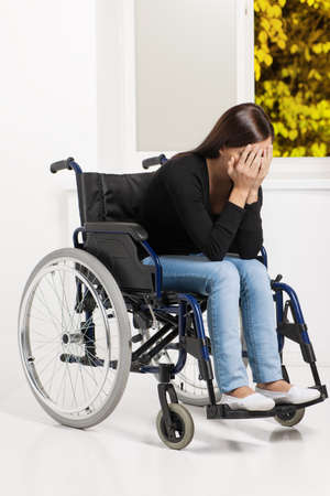long depression: Women with disability. Depressed young women sitting at the wheelchair and covering her face with hands
