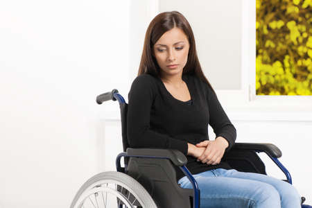 Women with disability. Depressed young women sitting at the wheelchair and looking away photo
