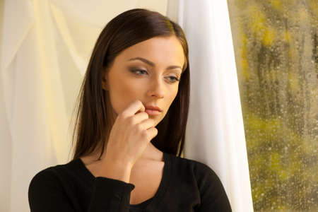 Thoughtful women. Thoughtful young women standing in front of the window and holding her hand on chin Stock Photo