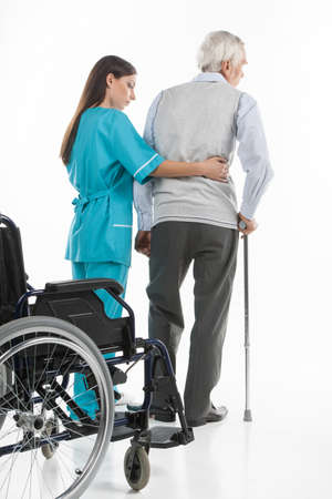 home care nurse: Senior care. Confident nurse helping senior men to walk while isolated on white