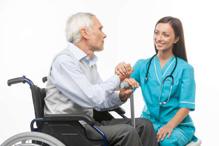medical worker: Senior care. Cheerful young nurse holding senior man hand and smiling while isolated on white