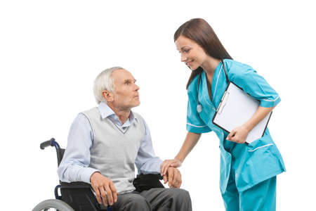 nurse clipboard: Senior care. Confident young nurse holding senior man hand and smiling while isolated on white