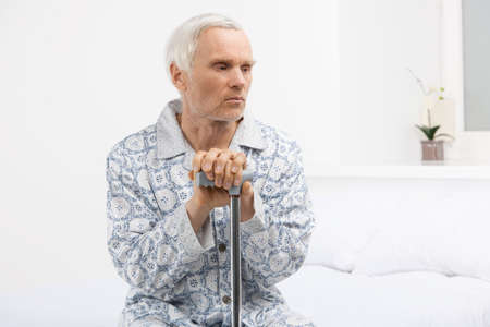Loneliness. Depressed senior man leaning at his cane while\ sitting on the bed
