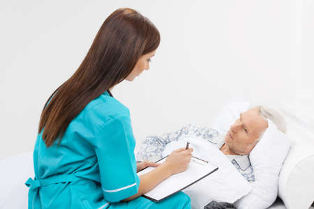 Taking care of seniors. Confident young nurse sitting near the patient lying on the bed and writing something in her note pad