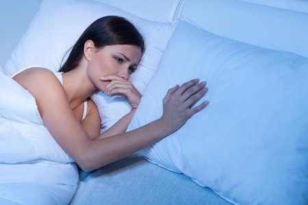 mujer llorando: Lo que falta. Mujeres jóvenes deprimidos tumbado en el sofá y la celebración de la mano en la almohada Foto de archivo