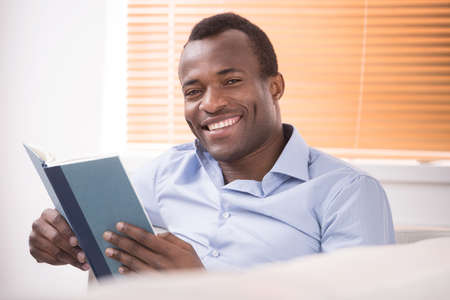 Reading an exciting book. Cheerful African descent reading a book and smiling at camera photo
