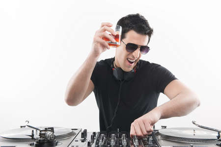 Cool DJ at the turntable. Happy young men spinning on turntable and drinking while isolated on white photo
