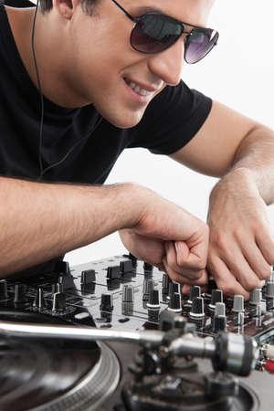 electric fixture: DJ al giradischi. Fiducioso giovane DJ filatura su giradischi mentre isolato su bianco