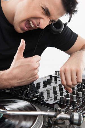 electric fixture: Cool music. Fiducioso giovane DJ di filatura su giradischi e gesticolare mentre isolato su bianco