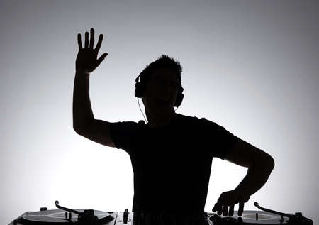 producers: DJ silhouette. Silhouette of DJ gesturing and spinning on turntable Stock Photo