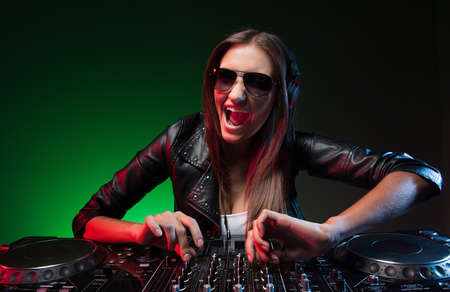 dj turntable: Female DJ. Happy young female DJ in sunglasses playing music and smiling at camera Stock Photo