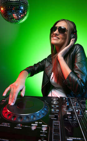 Female DJ at work. Beautiful young female DJ in headphones spinning on  turntable photo