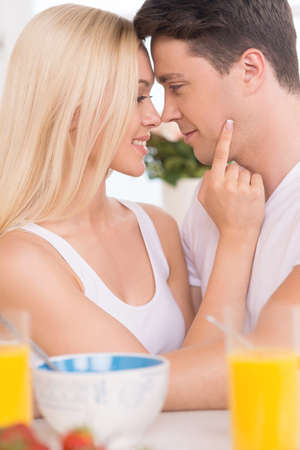 Loving couple. Young loving couple looking at each other while having breakfast together photo