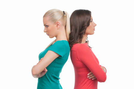 Women confrontation. Two angry women standing back to back and holding their arms crossed while isolated on white
