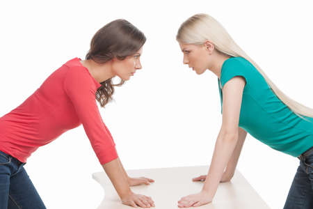 Women confrontation. Two angry women looking at each other while holding their hands on the table