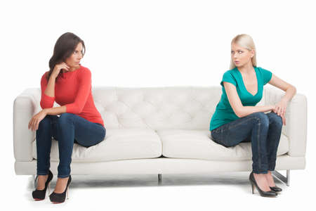 Not friends anymore. Two angry women looking at each other while sitting on the different sides of a couch photo