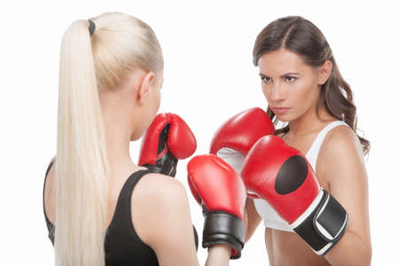 Women boxing. Two confident women boxing while standing isolated on white photo