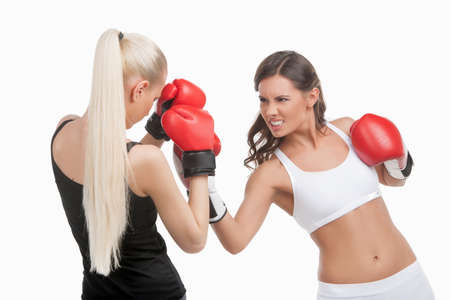Women boxing. Two young confident women boxing while isolated on white photo