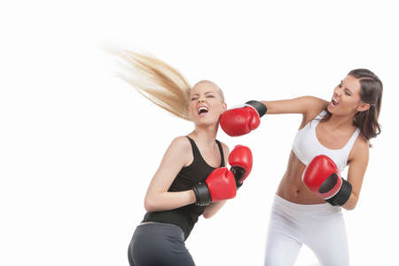 Two women boxing. Two young women boxing while isolated on white photo