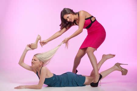 mujeres peleando: Estos zapatos son los míos! Es la mía! Dos mujeres jóvenes enojados lucha por los zapatos mientras aislados sobre fondo rosa