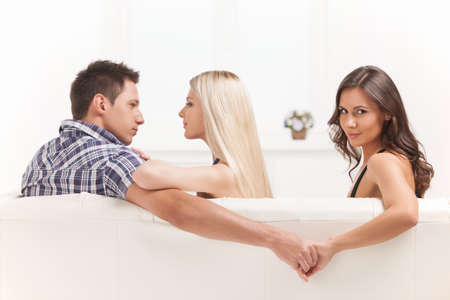 Love triangle. Beautiful young women holding hands with men sitting near his girlfriend photo