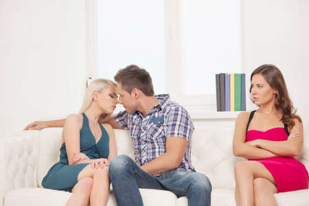 relationship problems: Jealousy. Young sad women sitting on the couch with her arms crossed while another women and men hugging near her