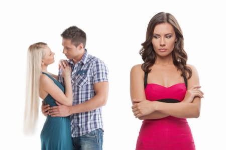 relationship problems: Loneliness. Young sad women standing with her arms crossed while another women and men hugging