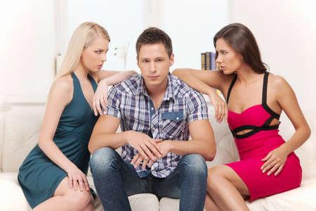 haciendo el amor: Love Triangle. Dos mujeres enojadas mirando el uno al otro mientras que los hombres sentado entre ellos
