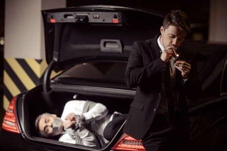 tied down: Kidnapped man. Tied up businessman lying in the car trunk and looking at camera while kidnapper smoking a cigar near him Stock Photo
